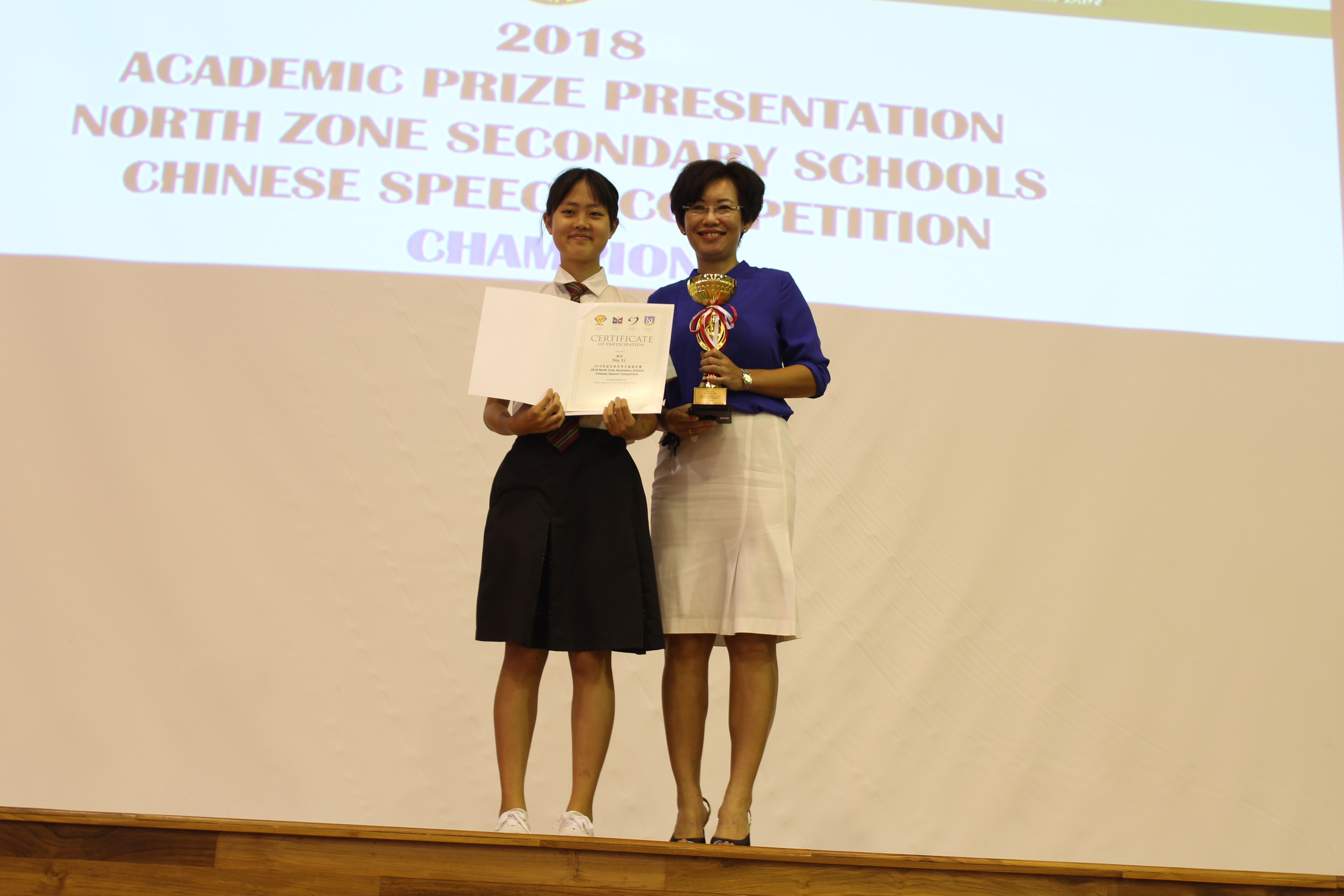 Nie Yi being awarded the champion trophy from Mdm Tan.JPG
